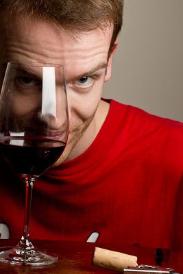 Photo of Old Parn (Tom Parnell) looking, in arch fashion, through a glass of red wine. He's got a red T-shirt on.