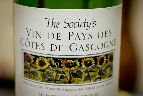 Closeup of the label of a bottle of Cotes de Gascogne from The Wine Society. The label has a picture of a row of sunflowers.