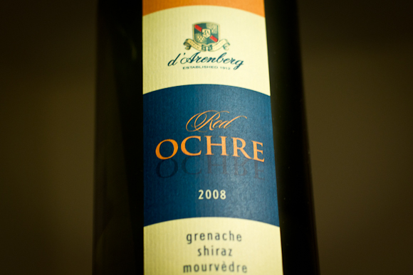 The label of a bottle of d'Arenberg Red Ochre, with distinctive organge/cream/blue colour bands and the d'Arenberg crest