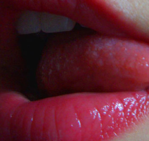 A cropped photograph of a woman sexily licking her brightly-lipsticked lips