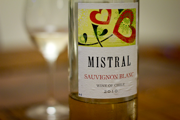 A bottle of Mistral Sauvignon Blanc in the foreground, with colourful abstract art on the label. In the background (out of focus) a glass of white wine.