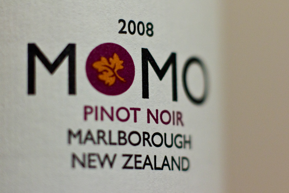 Closeup of the logo on a bottle of Momo Pinot Noir from New Zealand. A simple typographic logo with lots of white space. Gill Sans is the font, or something like it.
