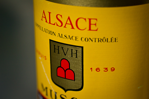 Closeup of the label of this Alsace Muscat. Bright, bright yellow label, with bold red and black type and crest
