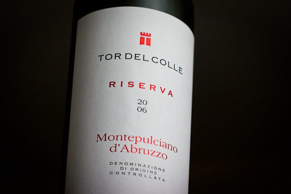 The label of Tor del Colle from Montepulciano DOC. The label is typographic in nature, with elegant, refined design in two colours (black and a metallic plum shade)