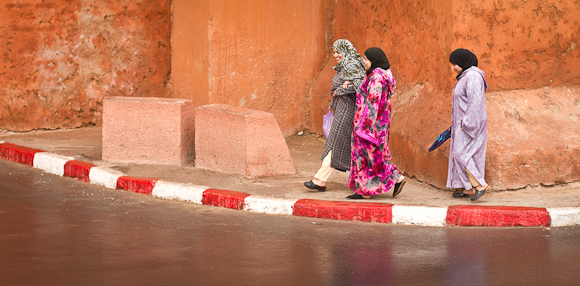 Three women in colourful Moroccan dress walk along a road shiny with recent rainfall