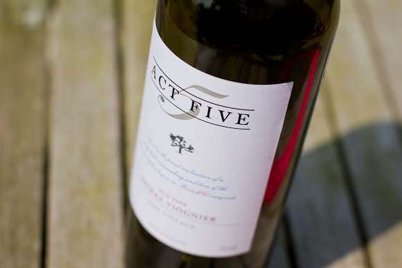A bottle of Act Five in the sunshine, on a wooden garden table