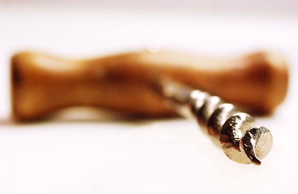 Macro photograph of a wooden-handled corkscrew. The metal screw is in focus; the wooden handle out.