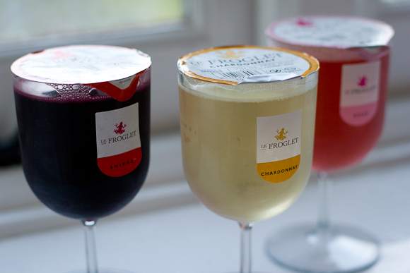 Three plastic cups of Le Froglet wine, sold by the glass — one red, one white, one rose