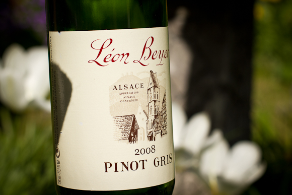 A bottle of Leon Beyer Pinot Gris. The label is adorned with cursive script and a line drawing of a chateau. In the background, out of focus flowers and greenery