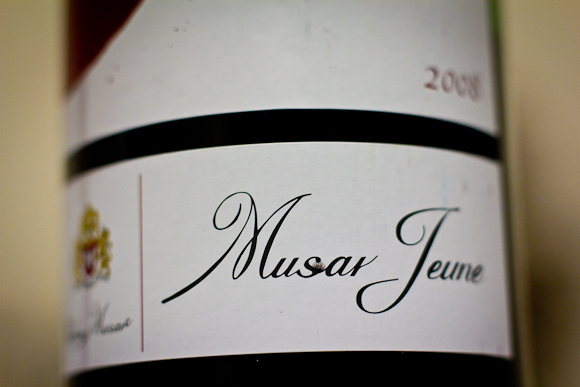 Macro closeup of the label of a bottle of Musar Jeune from Chateau Musar in Lebanon. Cursive typeface adorns a white label