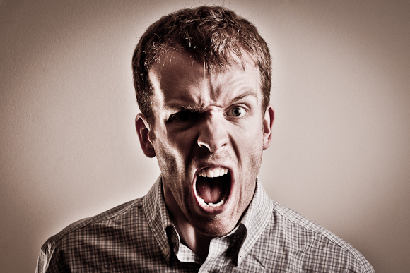 A high-contrast photo of a youngish man shouting a swearword at the camera