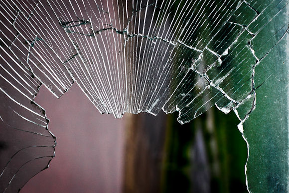 A splintered pane of glass makes a crescent. In the background, obscure, dark colours