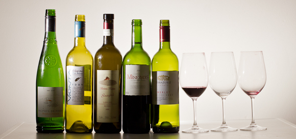 A line of five empty (or half-empty) wine bottles and three mostly-empty wine glasses