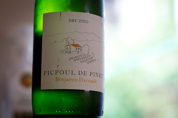 A condensation-misted bottle of Picpoul de Pinet: vibrant green bottle; label with simple line drawing of vineyards