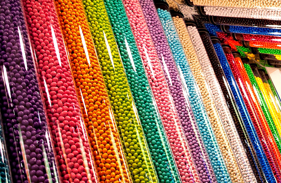 Numerous tubes of multicoloured sweets, arranged in a rainbow.
