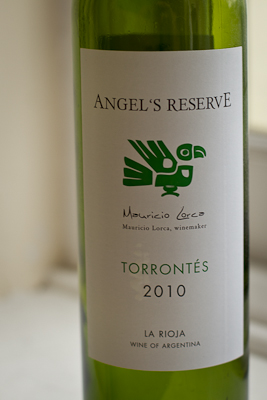 A bottle of Angel's Reserve: simple white label with a green piece of tribal-looking art (a drawing of a bird)