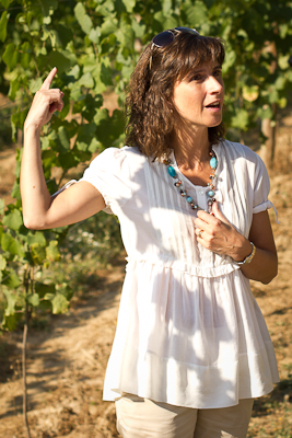 A woman dressed in white gesticulates, describing her vineyard (shown in the background)