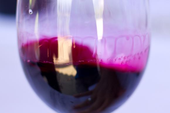 A shocking vermillion hue of wine swirled around a glass — inky stains