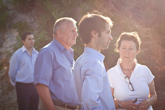 A group of people bathed in warm evening sunlight — backlit with lens flare