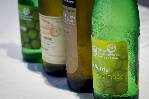 Four bottles of Vinho Verde white wine on a white tablecloth, condensation-misted