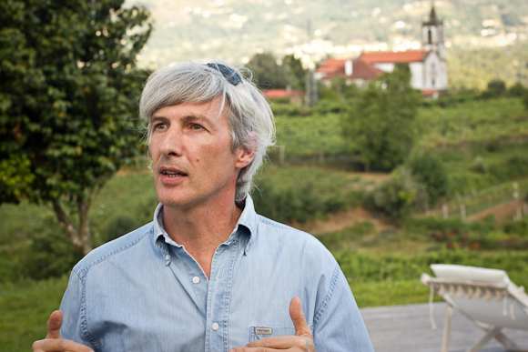 Portrait of Vasco Croft, talking to an audience, off-camera. In the background, out of focus, Vinho Verde countryside, a spired church, bathed in evening sunlight