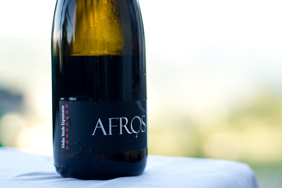 A bottle of Afros sparkling wine, black-labeled, on a white tablecloth
