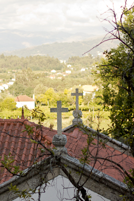 Two crosses on a red-tiled roof and, in the background, a view of sun-bathed countryside, hills and sky