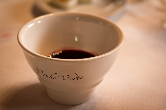 A white bowl containing dark red wine. 'Vinho Verde' is written on the side