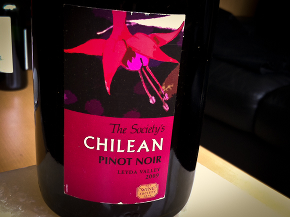 A closeup of the magenta-dominated label of the Wine Society's Chilean Pinot Noir. The label bears an image of a flower.
