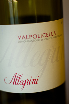 The label of a bottle of Allegrini: red and grey lettering on a neutral background