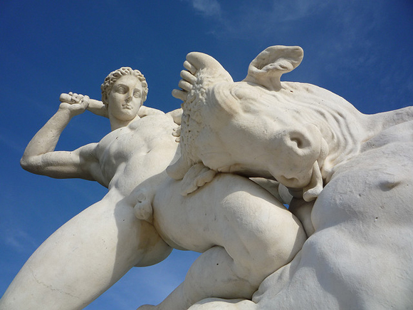 Dramatically angled photo of a statue in which a naked Theseus slays the Minotaur