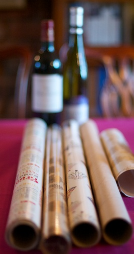 Two out-of-focus bottles of wine in the background; in the foreground, rolls of wrapping paper on a festive red tablecloth