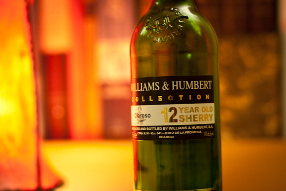 A half bottle of Williams & Humbert, bathed in red light