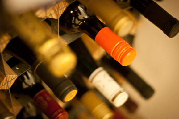 Shallow depth-of-field shot of the necks of wine bottles protruding from a wine rack