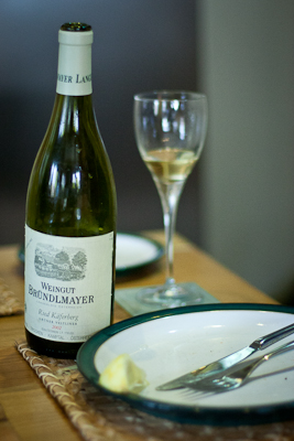 A bottle of Brundlmayer Gruner Veltliner on a table, alongside glass, plate and squeezed lemon slice