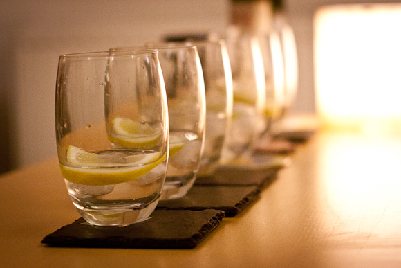 A line of six tumblers of gin and tonic, receding into the distance