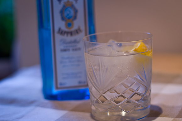 A cut-glass tumbler of gin and tonic, with an out-of-focus blue bottle of Bombay Sapphire gin in the background