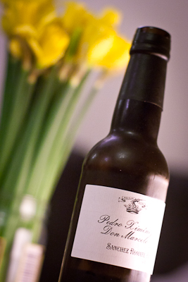 A dark brown bottle of Pedro Ximenez sherry, with out of focus daffodils behind