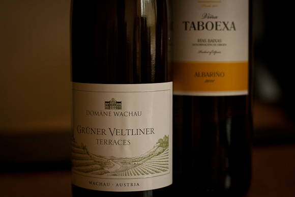 Two bottles of wine (a Gruner Veltliner and an Albarino) standing side by side