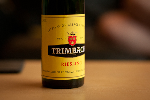 A half bottle of Trimbach Riesling, with distinctive bright yellow label, sits on a tabletop