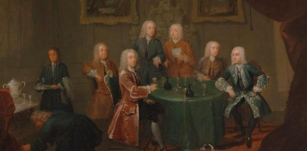 18th century painting of aristocrats gathered around a table drinking wine