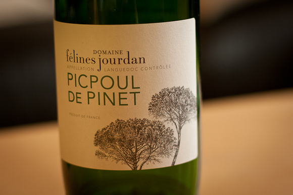 The label of this bottle of Picpoul de Pinet features elegant typography and simple silhouette images of trees