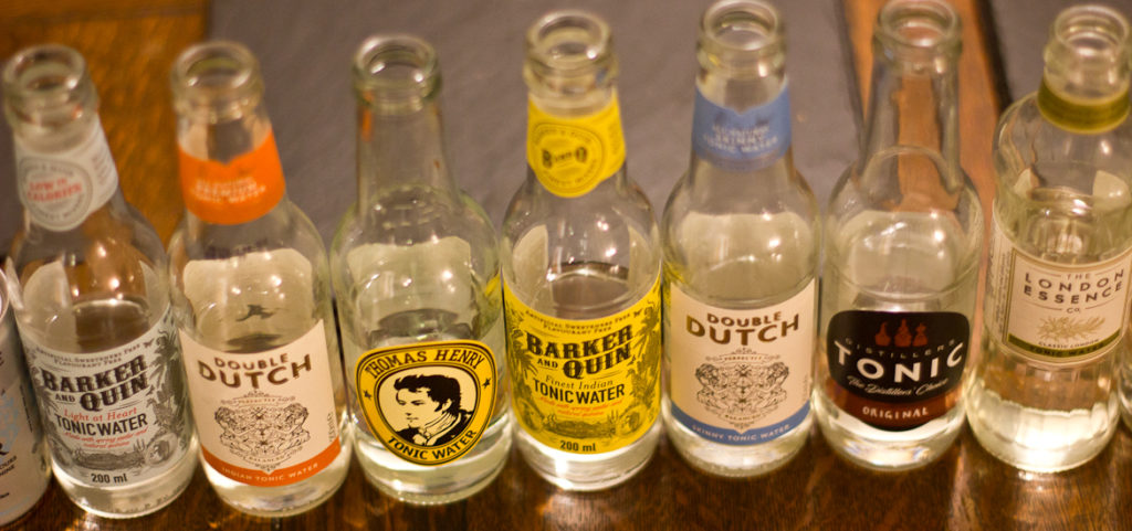 Bottles of tonic water in a line. Lots of different brands.
