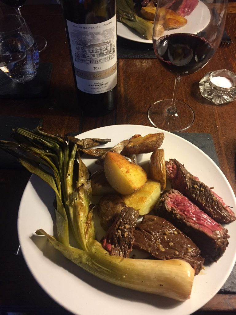 Bottle of Cahors. Bloody rare chunks of bavette steak. A*