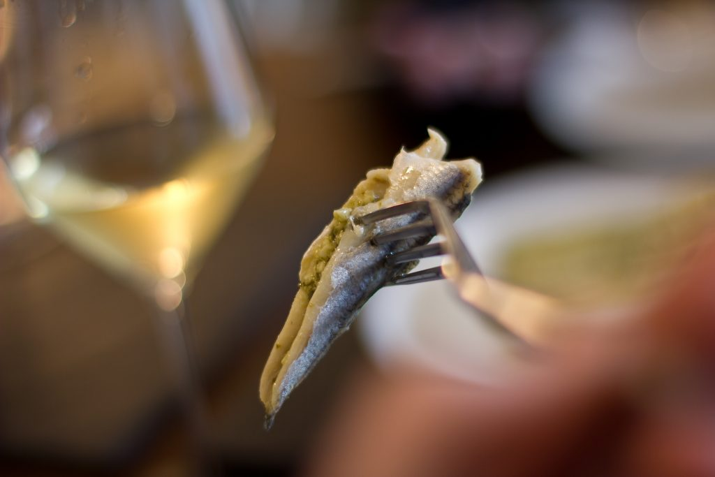 An anchovy on a fork. Glass of sherry in the background.