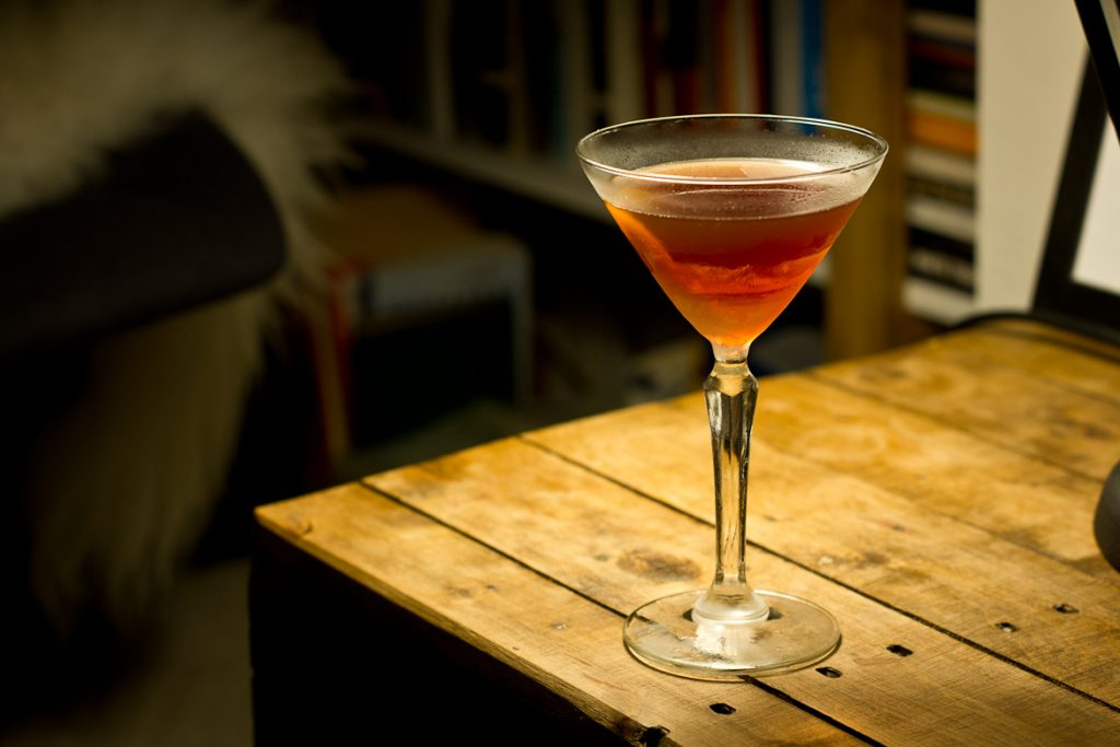 Hanky Panky cocktail in a martini glass with twist of orange. Made from gin, vermouth and fernet.