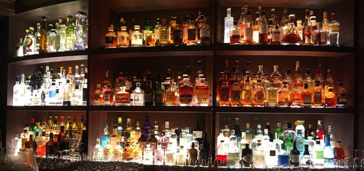 A huge selection of spirits lined up and beautifully lit in Hide Below bar in London