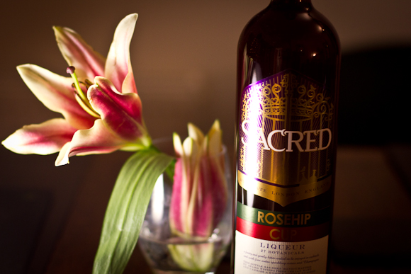 Bottle of Sacred Rosehip Cup and a lily in a glass