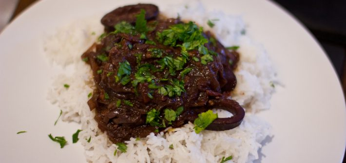Dark squid stew on a plate with rice