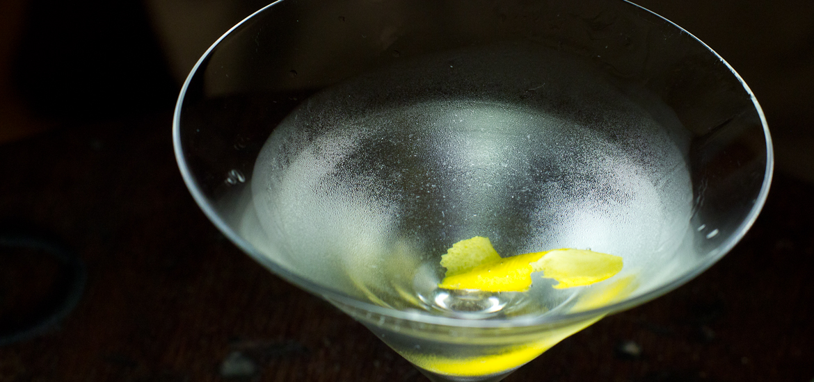 A closeup shot of a gin martini, ice-cold, in a martini glass with lemon twist
